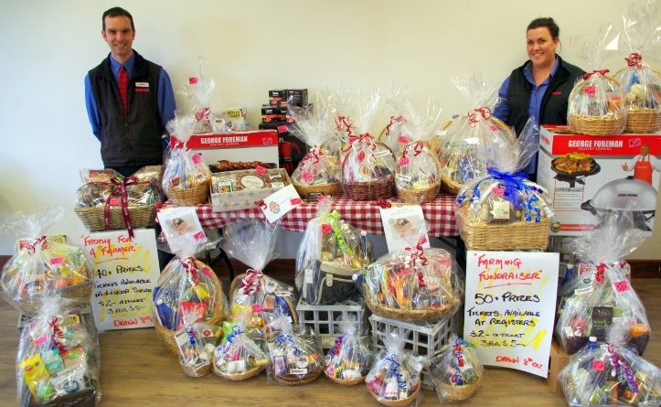 Maxi IGA Castlemaine store manager Josh Kerin and duty manager Michelle Whaley with some of the raffle hampers on display.