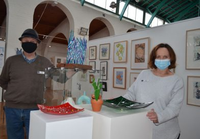 Castlemaine Visitor Centre volunteers Michael and Claire are pictured with some of the beautiful artworks on display at the Historic Market Building.