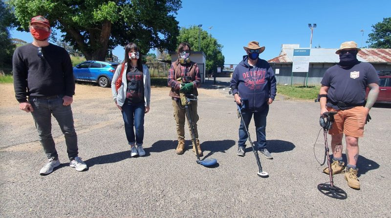 Local couple Piers and Emma and volunteers Deb Lorenz, Wayne Taylor and Chris Cook with metal detectors in hand search for the ring at the Camp Reserve last Saturday.